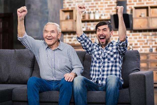 Веселый отец и его сын отдыхают дома во время просмотра футбола