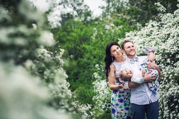 Веселый отец и мать весело играют со своей маленькой дочкой. семья отдыхает на природе среди кустов спиреи.