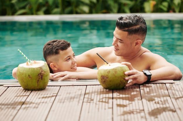 Веселые отец и сын проводят время вместе, они стоят в бассейне и пьют сладкие кокосовые коктейли