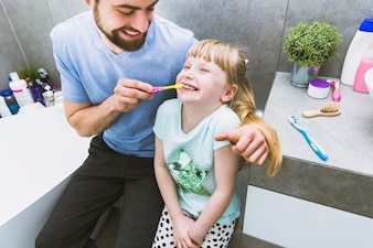 Cheerful father helping daughter to brush teeth