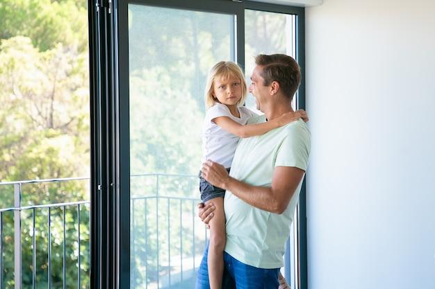 Веселый отец держит милую дочь, глядя на нее и улыбаясь