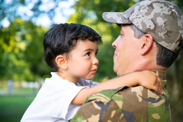 Padre allegro che tiene il piccolo figlio in braccio, abbracciando il ragazzo all'aperto dopo il ritorno dal viaggio di missione militare. colpo del primo piano. ricongiungimento familiare o concetto di ritorno a casa