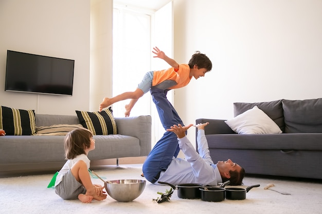 Cheerful father holding son on legs and lying on carpet. happy caucasian boy flying in living room with help of dad. cute boy sitting on floor near bowl and pans. childhood and weekend concept
