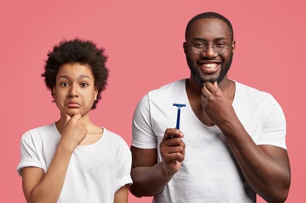 Веселый папа держит бритву, трогает густую бороду, советует подростку, как правильно бриться