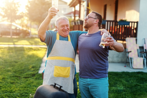 Cheerful father in law and son in law hugging and drinking beer while standing next to grill in backyard. family gathering concept.