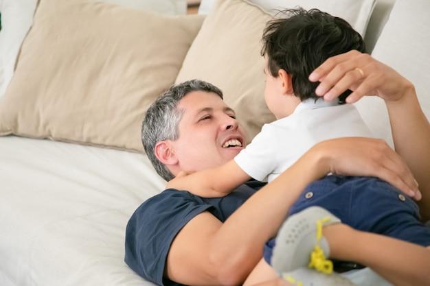 陽気な父親が愛らしい男の子とソファーに横になっています。