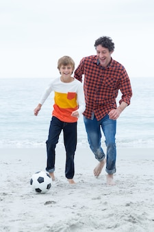 Cheerful father and son playing at sea shore