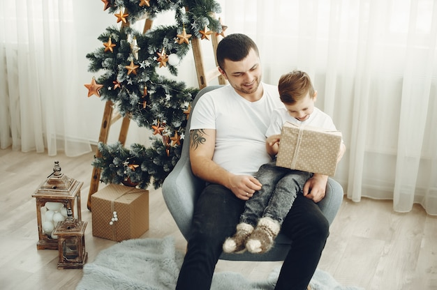 Cheerful father and son sitting near christmas decorations. the boy is sitting with joy