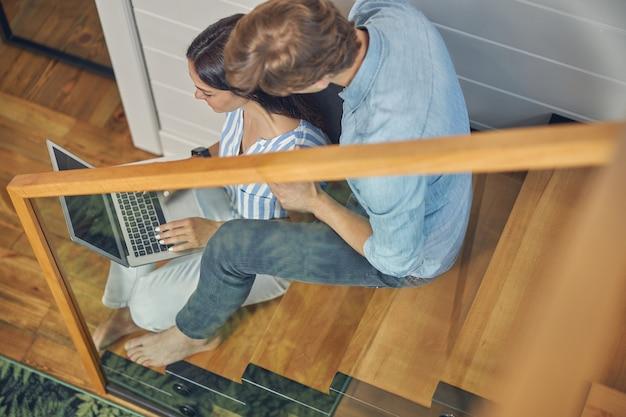 노트북의 화면을 보면서 나무 계단에 앉아 캐주얼 옷을 입고 쾌활한 여성과 잘 생긴 남자