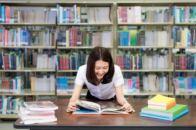 Cheerful female asian student reading book during break between lesson near bookshelves