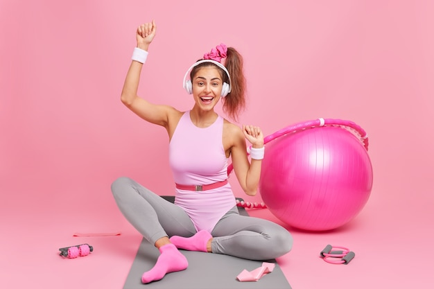 Cheerful female athlete with pony tail in activewear enjoys favorite playlist via wireless headphones poses on fitness mat has training at home surrounded by sport equipment