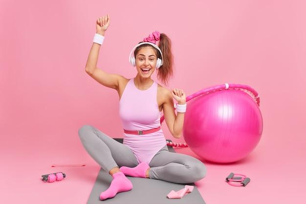 활동복을 입은 쾌활한 여성 운동선수는 무선 헤드폰 포즈를 통해 좋아하는 재생 목록을 즐깁니다. 피트니스 매트에서 스포츠 장비로 둘러싸인 집에서 훈련을 하고 있습니다