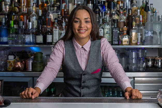 Cheerful female bartender standing behind counter in bar