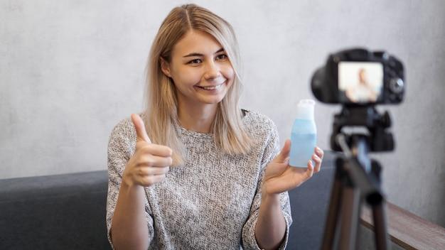 Веселая женщина-красотка-блоггер записывает видео дома. она показывает лосьон для кожи и знак как от руки