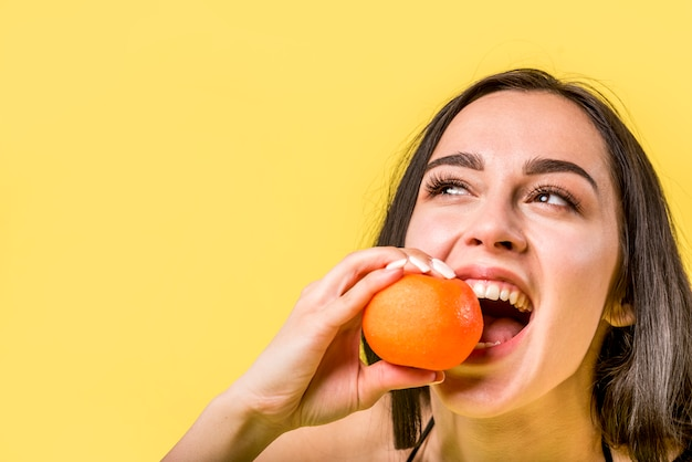 Cheerful female biting tangerine