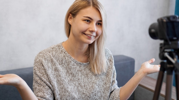 Cheerful female blogger recording video at home