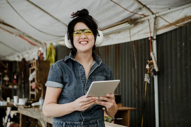 Веселая женщина-плотник с защитными наушниками с помощью планшета в мастерской