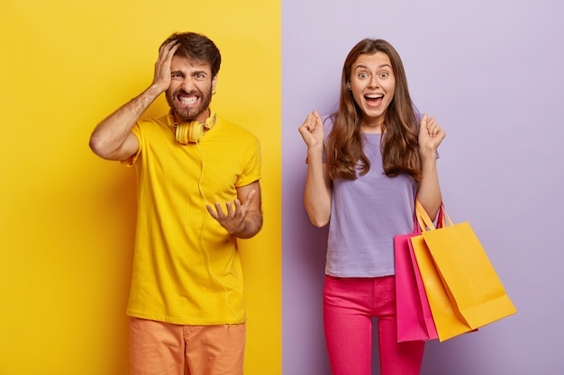 Cheerful female carries colorful shopping bags, rejoices new purchase, clenches fists with joy, annoyed husband feels angry with wife shopaholic, gestures with irritation