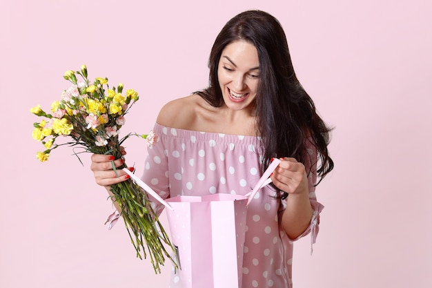Cheerful female celebrates birthday, looks with happiness and surprise at gift bag, rejoices recieving present, holds beautiful flowers