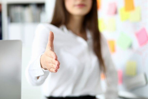 Cheerful female clerk welcoming business partner