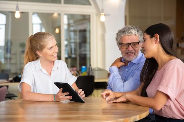Веселая женщина-консультант и молодые и зрелые клиенты смотрят и обсуждают презентацию на планшете, улыбаются и разговаривают