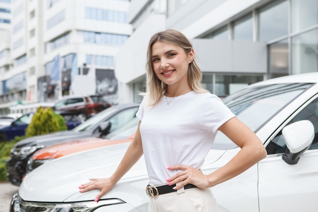Cheerful female customer at outdoor car dealership parking