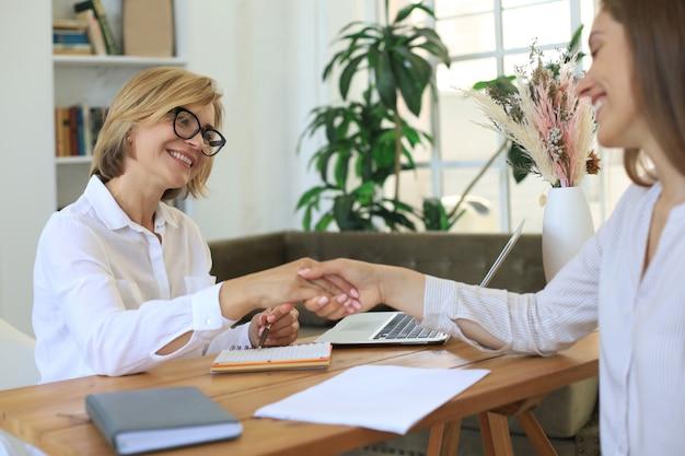 쾌활한 여성 의사 심리학자는 상담 회의를 한 후 감사하는 환자와 악수합니다.