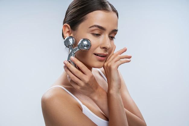 현대적인 장치로 얼굴 마사지를 하는 쾌활한 여성