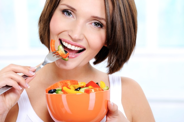 陽気な女性が野菜サラダを食べる