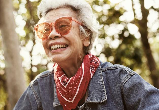 A cheerful female elderly in denim jacket