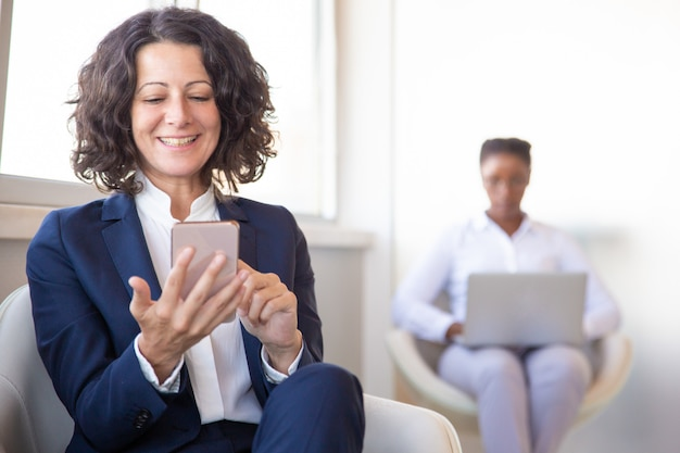 Cheerful female employee watching content on cell