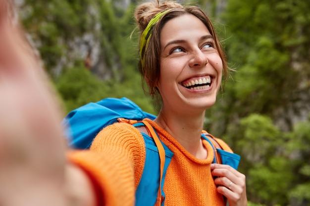 Un'esploratrice allegra fa un viaggio meraviglioso nella foresta verde, allunga la mano per fare selfie, sta con lo zaino all'aperto, sorride ampiamente, concentrata da parte. persone