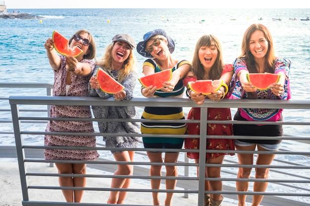 陽気な女性の友達は、友情の中で一緒に新鮮で健康的な赤いスイカを食べて夏のライフスタイルを楽しんで楽しんでいます