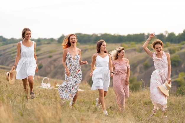 Cheerful female friends have a great time together on a picnic in a picturesque place overlooking the green hills. girls in white dresses dancing in the field