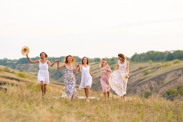 Cheerful female friends have a great time together on a picnic in a picturesque place overlooking the green hills. women in white dresses dancing in the field