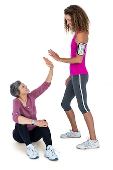 Cheerful female friends high fiving over white background
