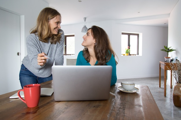 Cheerful female friends watching and discussing media content