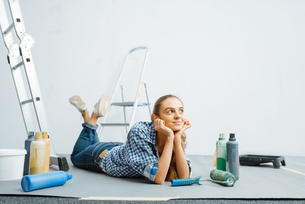 Веселая малярка лежит на полу. ремонт дома, счастливая женщина делает ремонт квартиры, ремонт украшения комнаты