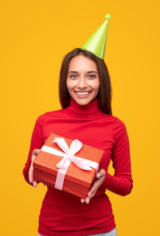 빨간색 터틀넥과 녹색 파티 모자에 쾌활한 여성이 카메라에 웃고 노란색 배경에 생일 축하 중 선물을 보여줍니다.