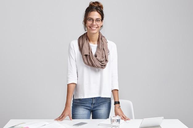 メガネで陽気な女性インテリアデザイナーは、彼女の職場に立っています。