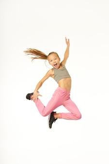 空中でジャンプし、彼女の足に手を置くスポーツウェアの陽気な女性の子供。白い背景で隔離