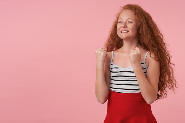 Жизнерадостная девочка с кудрявыми волосами смотрит в сторону с широкой приятной улыбкой, счастливо поднимает кулаки на розовом фоне, в красной юбке и полосатом топе