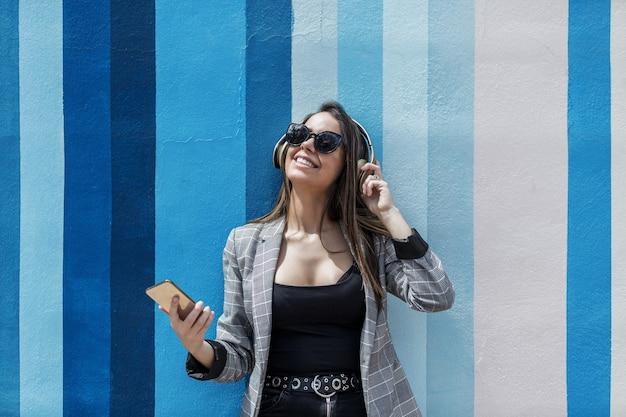 줄무늬 벽 근처 음악을 듣고 쾌활 한 여성