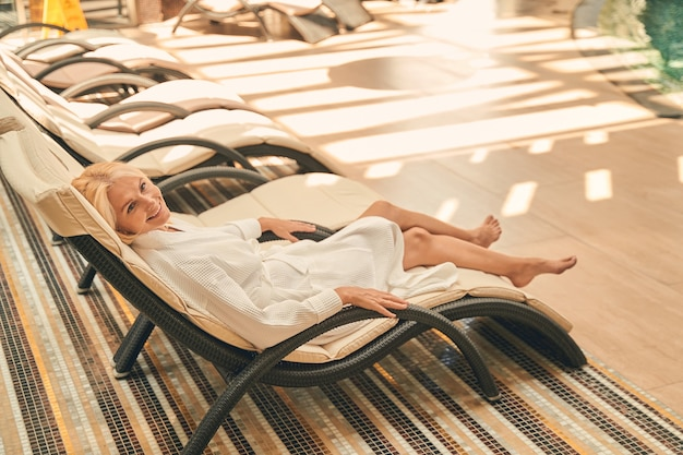 Cheerful female lying on the sun bed near the swimming pool in the resort hotel