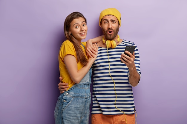 Cheerful female and male embrace and use modern smartphone, dressed in stylish clothing, isolated on purple wall
