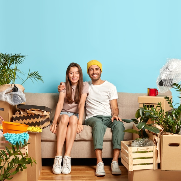 Cheerful female and male pose on couch, embrace and have fun together, move in new flat
