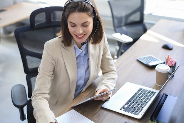 Веселая женщина-менеджер сидит за офисным столом и выполняет корпоративные задачи с помощью беспроводного подключения на цифровых гаджетах