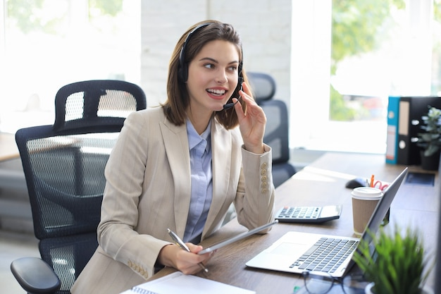 Cheerful female manager sitting at office desk and performing corporate tasks using wireless connection on digital gadgets