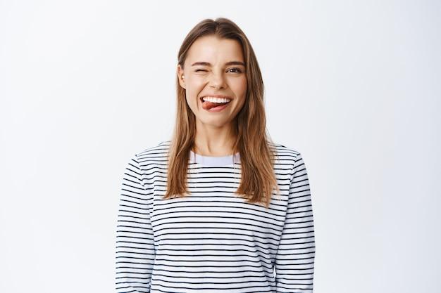 ブロンドの髪と白い笑顔の陽気な女性モデル、舌を見せて、正面でウインクをして興奮し、白い壁にカジュアルな服を着て立っています