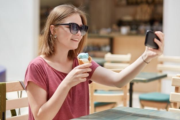 フレンドリーな笑顔で陽気な女性モデルはアイスクリームを食べるし、携帯電話でselfieの肖像画を作る